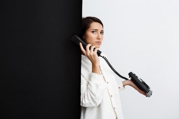 검은 색과 흰색 벽을 통해 오래 된 전화에 말하는 여자