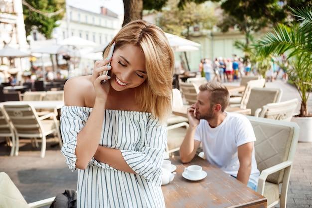 彼女のボーイフレンドが退屈している間、電話で話す女の子。