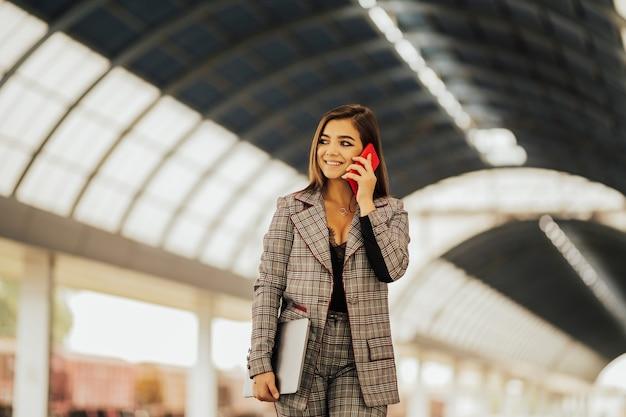 소녀는 휴대 전화, 미소 및 노트북을 들고 말한다