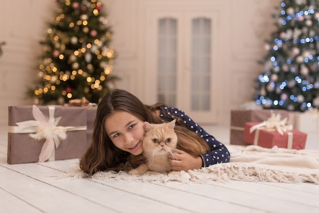 The girl spends the christmas holidays with her cat.
