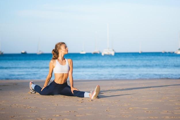 Girl splits on the beach. yoga on the beach in the morning