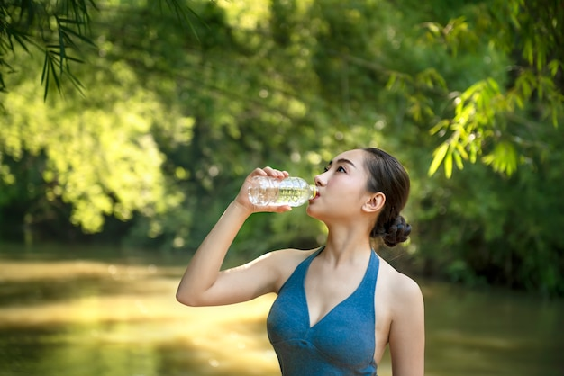Girl in sport clothes drinking water