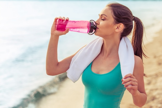 Girl in sport clothes holding a towel and drinking water.