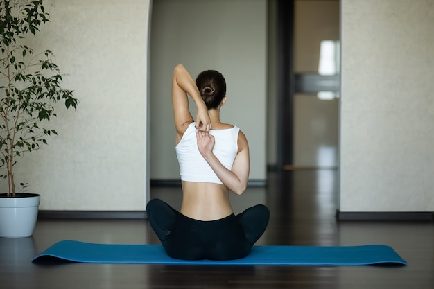 A girl on sport mat performs an exercise of hand to lock behind her back. view from the back.