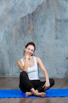 Ragazza in uniforme sportiva seduta su un tappetino da yoga blu dopo un duro allenamento.