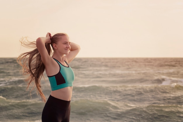 Girl in sports clothes on the beach adjusts her hair. morning light
