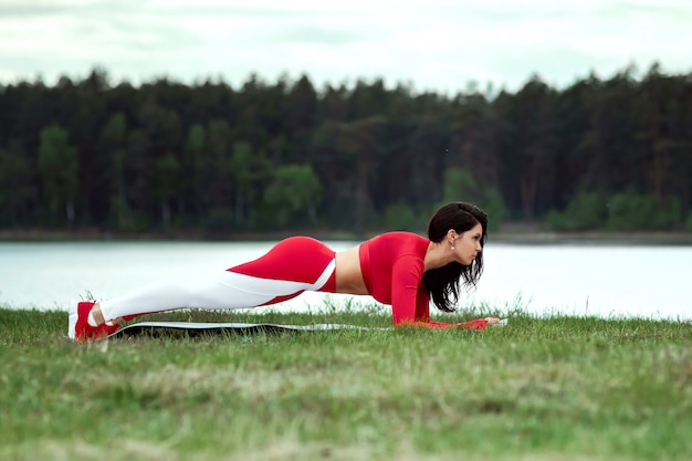 A girl in a sports suit does the bar, physical exercise on the abs on the background of nature. the concept of a healthy lifestyle, exercise, fresh air. copy space.