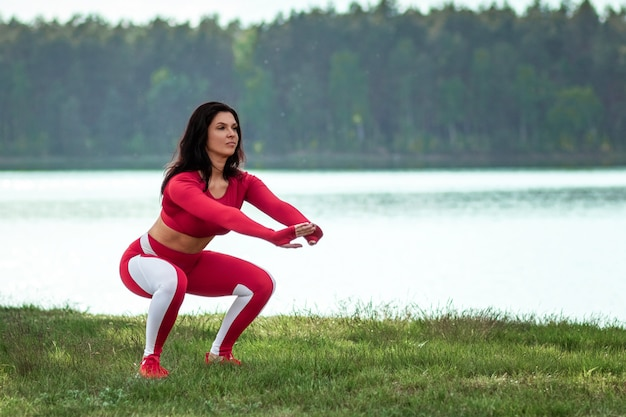 Girl in a sports suit does squats, physical exercises on a background of nature. the concept of a healthy lifestyle, exercise, fresh air. copy space.