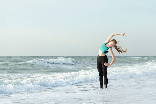 Girl in sportswear on the beach doing exercises. morning sun