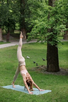 Girl in sportswear doing yoga in the summer in the park