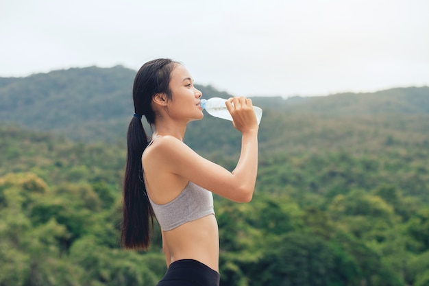 Girl in sportswear drinks water from recycled plastic bottle in park outdoors after training