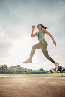 Girl in sportswear jogging on a treadmill at the stadium on a summer day