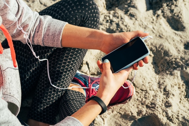 Girl in sportswear listening to music in headphones on a mobile phone on the beach in the morning