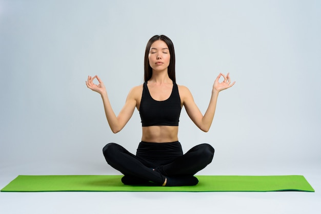 Girl in sportswear sits in lotus position with eyes closed.
