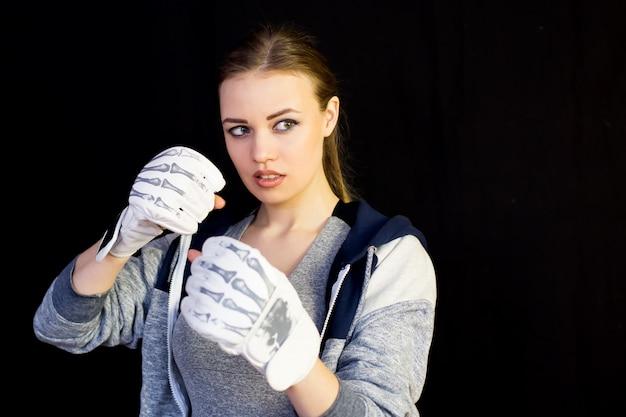 Girl sportswoman in gloves for boxing on black.