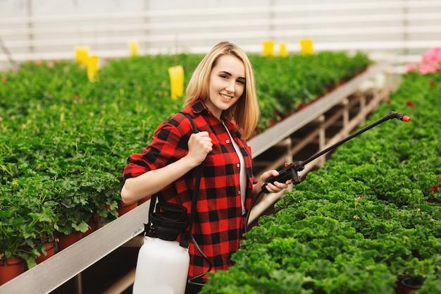 女の子は植物にスプレーします。温室で働く女の子。肥料植物