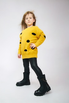 Girl in spring boot shoes posing in the studio on a white background. baby fashion beautiful clothes