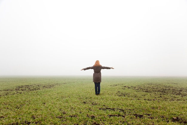 Girl at spring field in fog time.