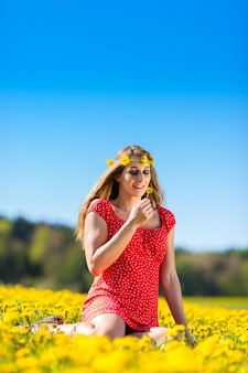Girl in spring on a flower meadow with dandelion