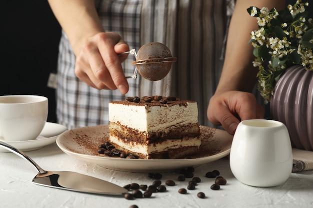 Девушка окропляет пудрой по тирамису. композиция с вкусным тортом на белом фоне
