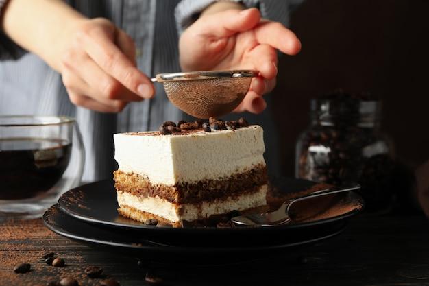 Девушка окропляет пудрой по тирамису. композиция с вкусным тортом на деревянном фоне