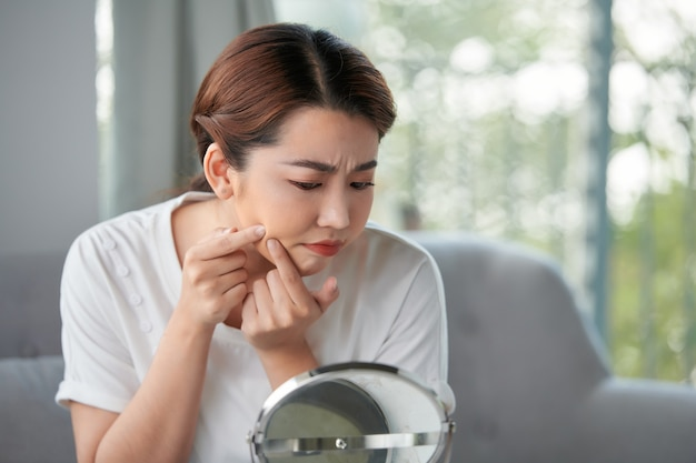 Girl squeezing pimple at home