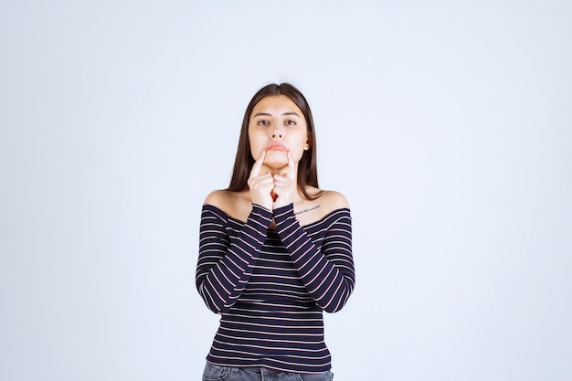 Girl in srtiped shirt looks ill and showing her mouth.
