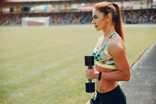 The girl at the stadium is playing sports