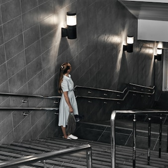 Girl on the stairs down, late transition, subway. one person on the descent into the underpass.