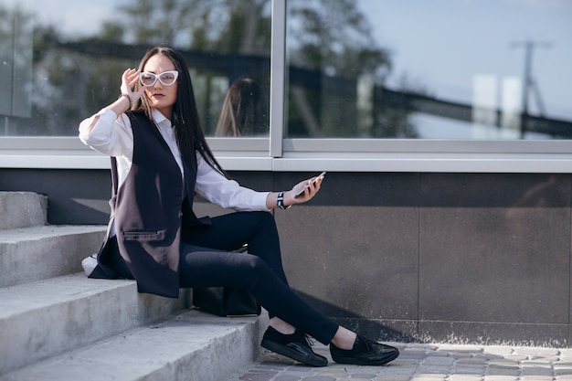 Girl on stairs with a mobile in hand and touching her glasses