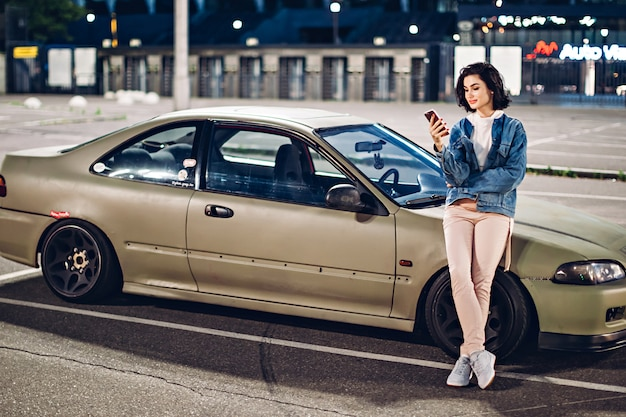 여자는 차 근처에 서 저녁에 스마트 폰을 사용