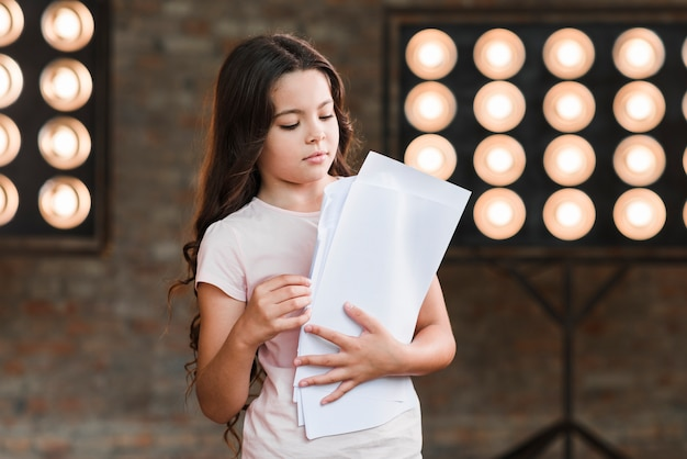 Girl standing against stage light holding scripts