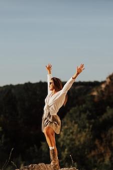山の晴れた日に大きな石の上に一人で立っている女の子