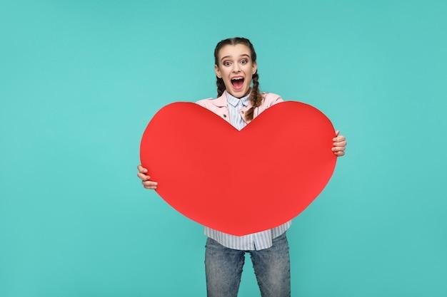 Девушка стоит и держит форму большого красного сердца и смотрит в камеру с удивленным лицом