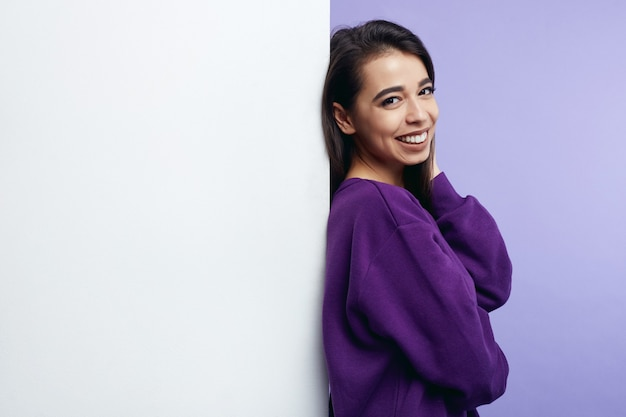 Девушка стоит и улыбается рядом с пустой белой стеной рекламного щита