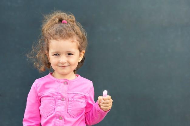 Девушка стояла у доски, держа в руке мел. ребенок идет в первый класс. обратно в школу.