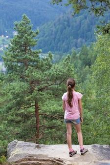 Девушка стоит у скалистого обрыва и смотрит на лесные горы