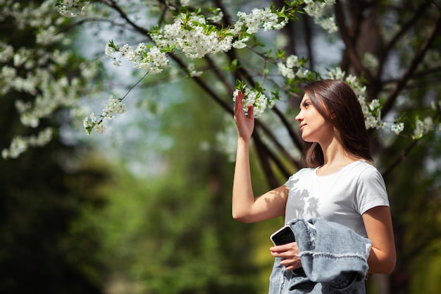 Girl standing under blossoming apple tree in natural park. fashion concept. elegant young lady in jeans clothes enjoying flowering garden at sunny spring day.natural beauty makeup. horizontal