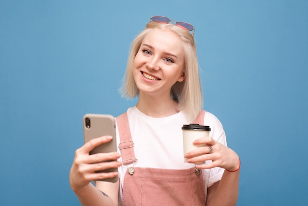 Girl standing on blue with a smartphone and a cup of coffee in hand, smiling, wearing a cute casual wear.