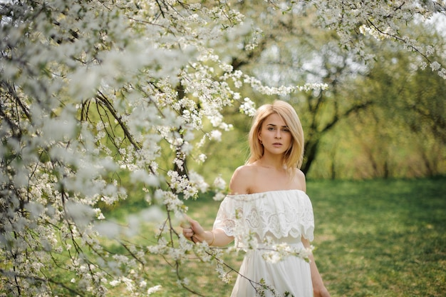 Girl standing between branches of beautiful white tree