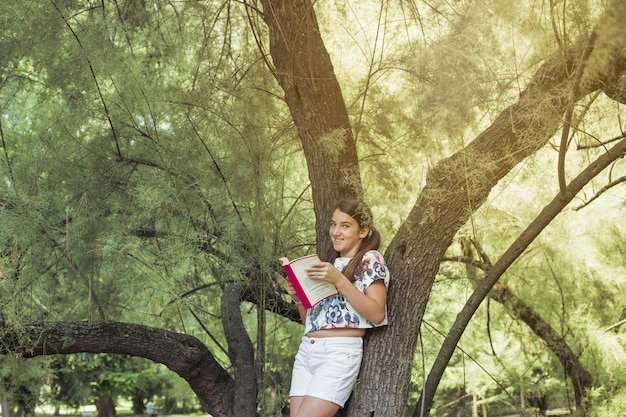 Girl standing by tree holding book smiling