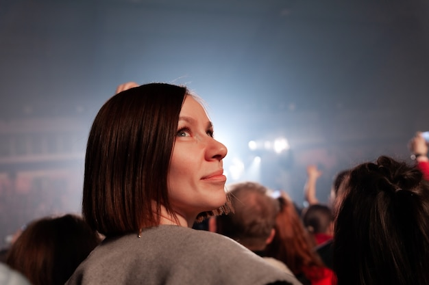 Girl standing at concert on background of people crowd and neon light