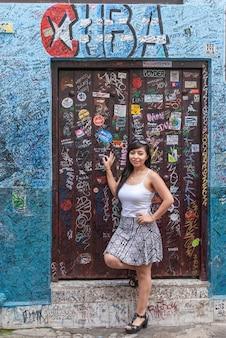 Girl standing in front of a door of la bodeguita del medio in havana cuba