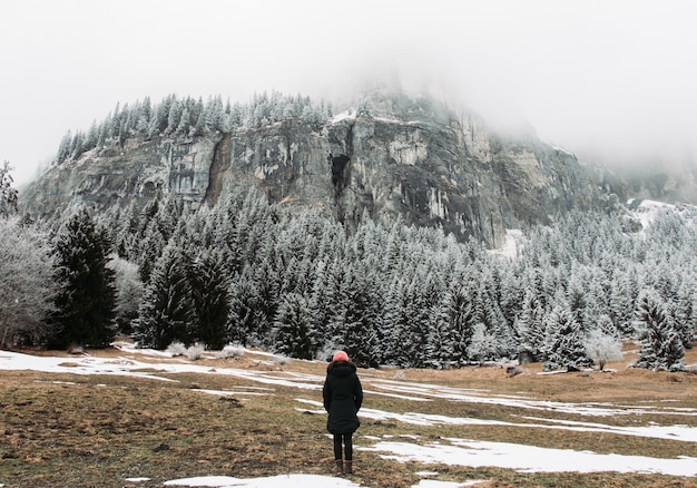 Girl standing in front of rocks and a forest covered in the snow under a cloudy sky