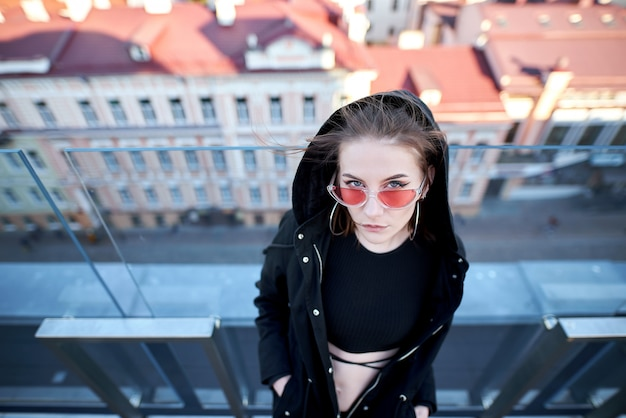 Girl standing at the glass fence and glass  is seen the city, in pink sunglasses.