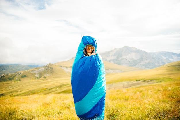 성격에 파란색 침낭에 서있는 여자