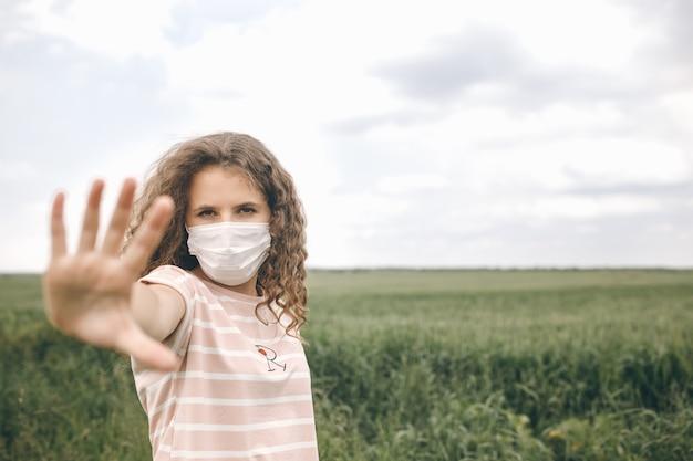 보호 마스크에 녹색 필드에 서있는 소녀는 코로나 바이러스를 막기 위해 손을 중지합니다.