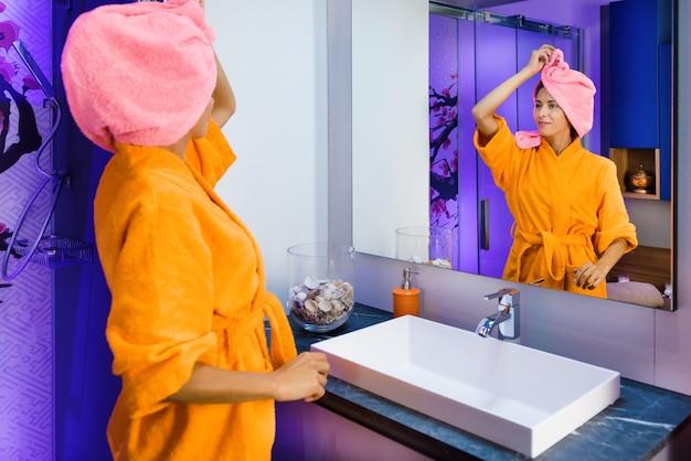 Девушка стоит в халате в ванной после утреннего душа