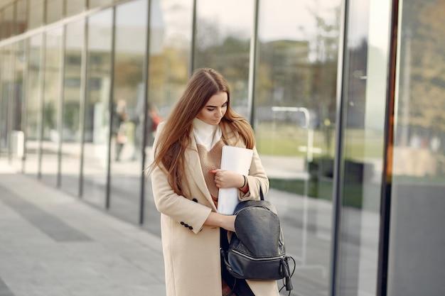 春の街に立っている女の子と彼女の手でドキュメントを保持