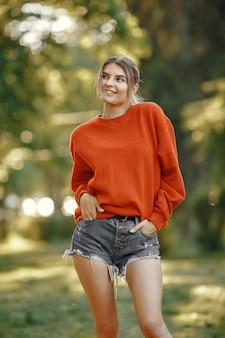 Девушка стоит в летнем парке